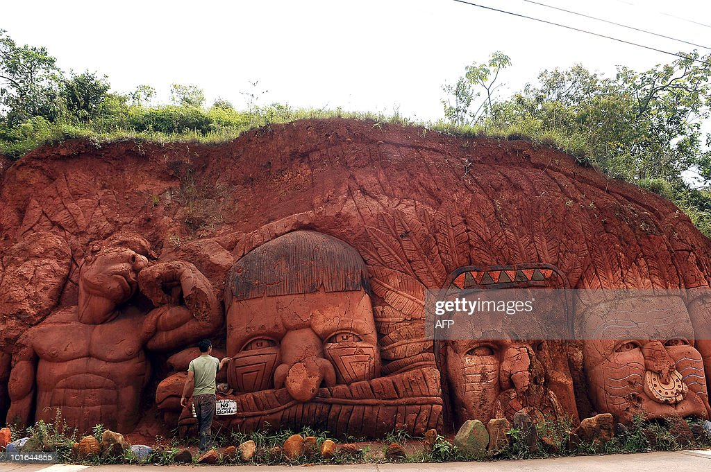 Colombian artist Carlos Andres Gomez works on a piece entitled 'Existence' during World Environment Day in Cali, Valle del Cauca departament, Colombia on June 5, 2010. Gomez sculpts figures on the mountain to raise awareness of the importance of the environment. AFP PHOTO/Luis ROBAYO