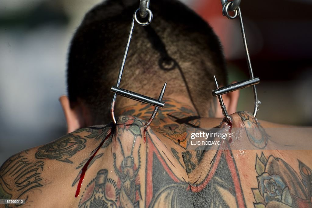 Colombian artist modifier of the body 'Damian Carnicero' hangs himself with hooks on his back during the Cali Tattoo Festival on September 12 in Cali...