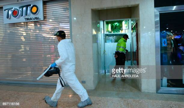 Colombian bomb squad officer and police invesigate after an explosion in a shopping center north of Bogota Colombia on June 17 2017 The blast killed...