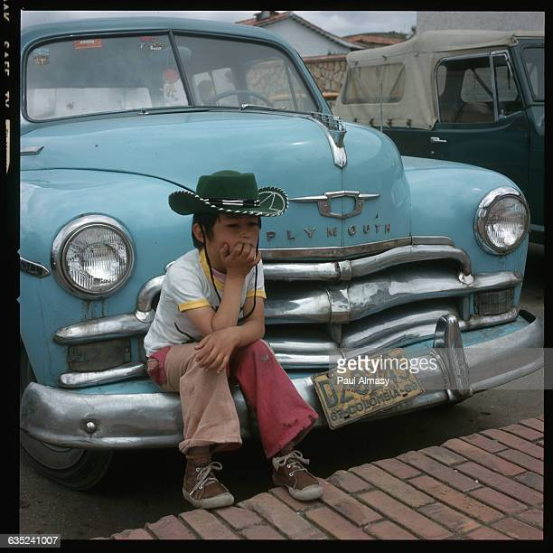 A Colombian boy wearing a green felt cowboy hat sits on the bumper of an old blue Plymouth