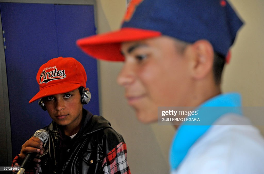 Colombian brothers Maicol (L) and Guiovanny Castro attend a class on April 26, 2016 in the municipality of Soacha, on the outskirts of Bogota, where an NGO promotes activities among some 300 at-risk children and teenagers. Through hip hop, graffiti art and other activities, the Proyecto de vida (Life Project) foundation - funded by Luxembourg NGO Children of Hope - is seeking to keep children in vulnerable situation away from drug addiction and crime. / AFP / GUILLERMO