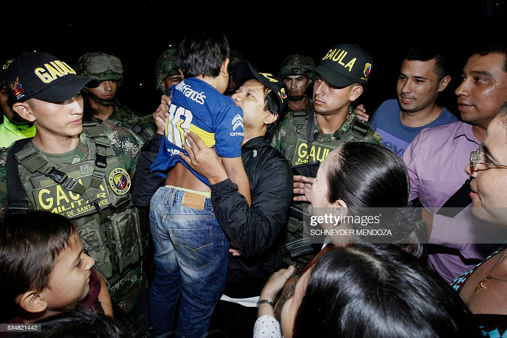 Colombian cameraman Carlos Melo, of Colombia's RCN television, greets relatives on arrival at the airbase of Cucuta, Colombia, on May 28, 2016 following his release after being held by the ELN guerrillas for four days in the restive region of Catatumbo, Norte de Santander deparment, bordering Venezuela. The journalists were investigating the disappearance of Colombia-Spanish journalist Salud Hernandez, who disappeared on May 21, 2016. The Colombian rebel group ELN freed two local TV reporters and prominent Spanish-Colombian journalist Hernandez Mora on Friday after holding them for days. / AFP / Schneyder Mendoza