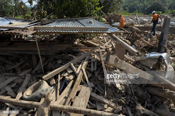 Colombian Civil Defense workers walk next to a house destroyed by mudslides caused by heavy rains in Mocoa Putumayo department Colombia on April 5...