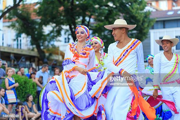 Colombian couples in traditional costumes dancing on folklore festival