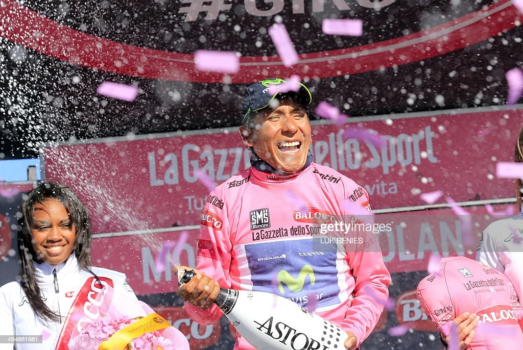 Colombian cyclist Nairo Quintana opens a bottle of champagne as he celebrates on the podium with the pink jersey of the overall leader after the 20th stage of the 97th Giro d'Italia, Tour of Italy, cycling race from Maniago to Monte Zoncolan on May 31, 2014. AFP PHOTO / LUK BENIES
