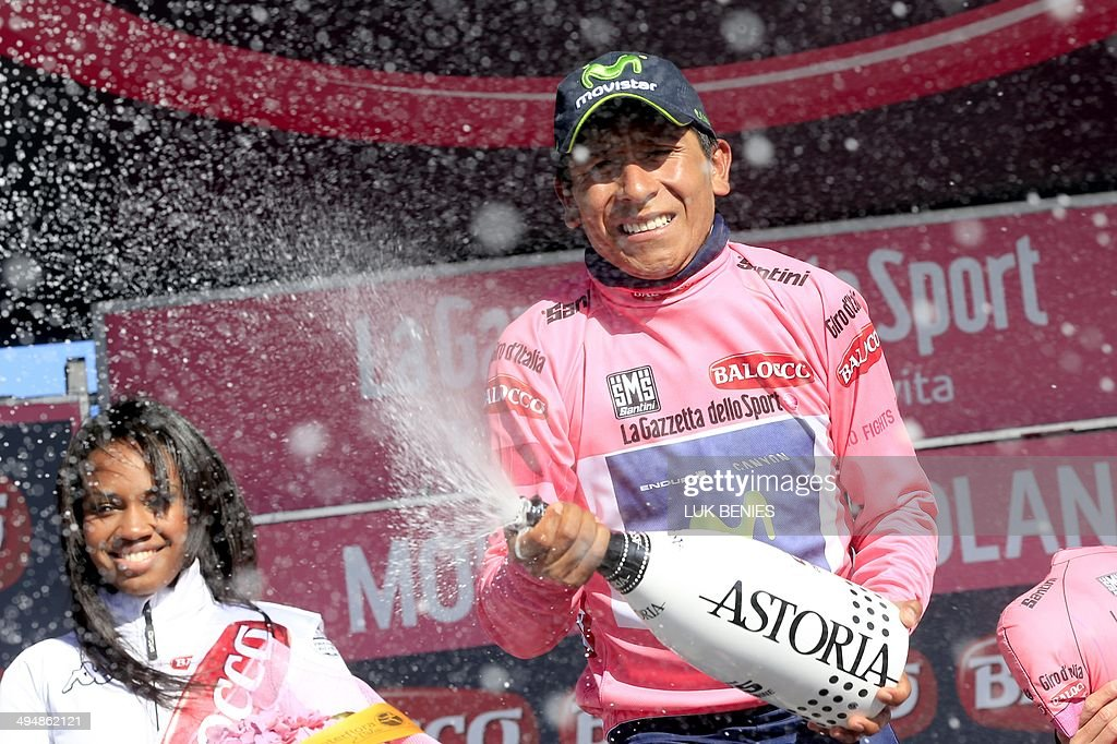 Colombian cyclist Nairo Quintana opens a bottle of champagne as he celebrates on the podium with the pink jersey of the overall leader after the 20th stage of the 97th Giro d'Italia, Tour of Italy, cycling race from Maniago to Monte Zoncolan on May 31, 2014.