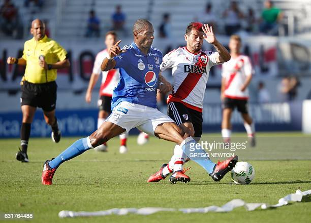 Colombian defender Andres Felipe Mosquera of Millonarios FC challenges forward Rodrigo Mora of Argentine club River Plate for the ball during their...