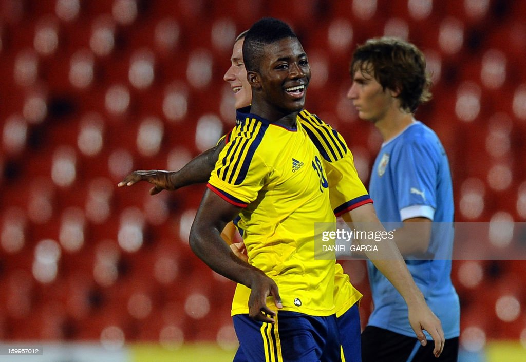 Colombian defenders Julian Figueroa and Andres Correa (L) gesture in celebration as they pass Uruguayan defender Guillermo Varella at the end of the match where Colombia defeated 1-0 Uruguay in the South American U-20 Championship in their final round football match at Malvinas Argentinas stadium in Mendoza on January 23, 2013. Four teams will qualify for the FIFA U-20 World Cup Turkey 2013.