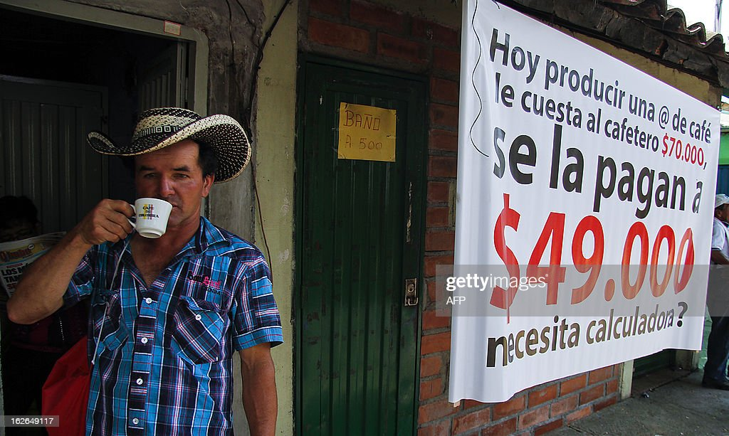 A Colombian farmer sips cofee during a march in protest during the first day of a national coffee producers' strike in Irra, Risaralda department, Colombia on February 25, 2013. Thousands of coffee farmers rallied and marched Monday in several towns of Colombia in protest against the economic difficulties of the sector which in recent years has seen falling prices and production, their leaders reported. AFP PHOTO/J.J Bonilla