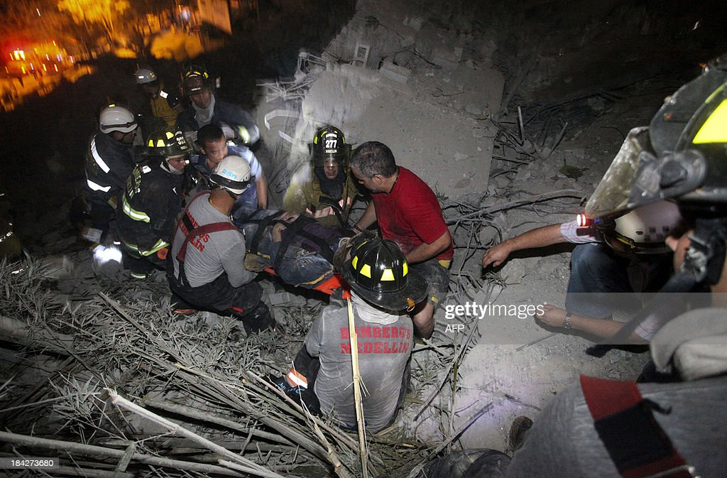 Colombian firefighters carry after a survivor on a stretcher from the debris after a building collapsed in Medellin, Colombia on October 12, 2013. Two people are injured and seven missing after a building collapse, officials said. AFP PHOTO / Robinson HENAO