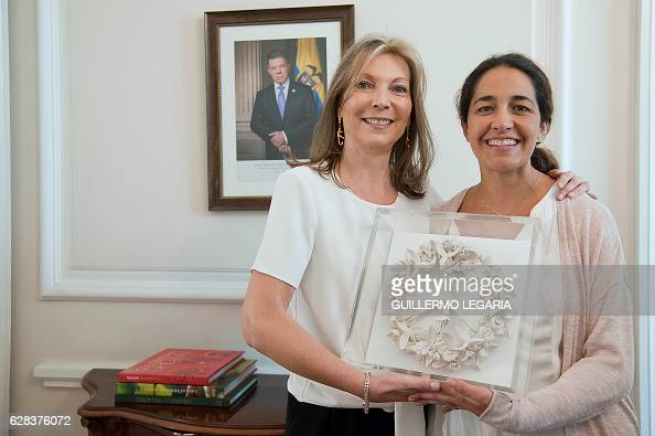 Colombian First Lady Maria Clemencia Rodriguez shows a work by Colombian artist Ana Gonzalez which she will give as a gift to the king of Sweden...
