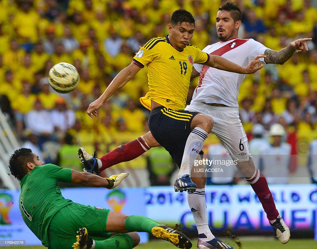 Colombian football player Teofilo Gutierrez (C) tries to score marked by Juan Vargas (R) and Peruvian goalie Raul Fernandez during their FIFA World Cup Brazil 2014 South American qualifier football match at Metropolitano stadium in Barranquilla on June 11, 2013.AFP PHOTO/Luis Acosta