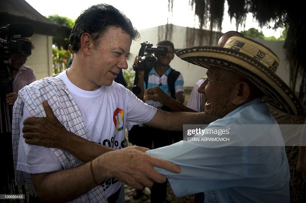 Colombian former Defense Minister and presidential candidate for the ruling National Unity party Juan Manuel Santos (L) is greeted by a supporter during a rally in Aracataca, department of Magdalena, Colombia's Caribbean Region on May 20, 2010. Colombia will hold the presidential elections next May 30, and according to polls, a run-off election between Colombian presidential candidate for the Green Party, Antanas Mockus and Santos will take place on June 20. AFP PHOTO/Eitan Abramovich