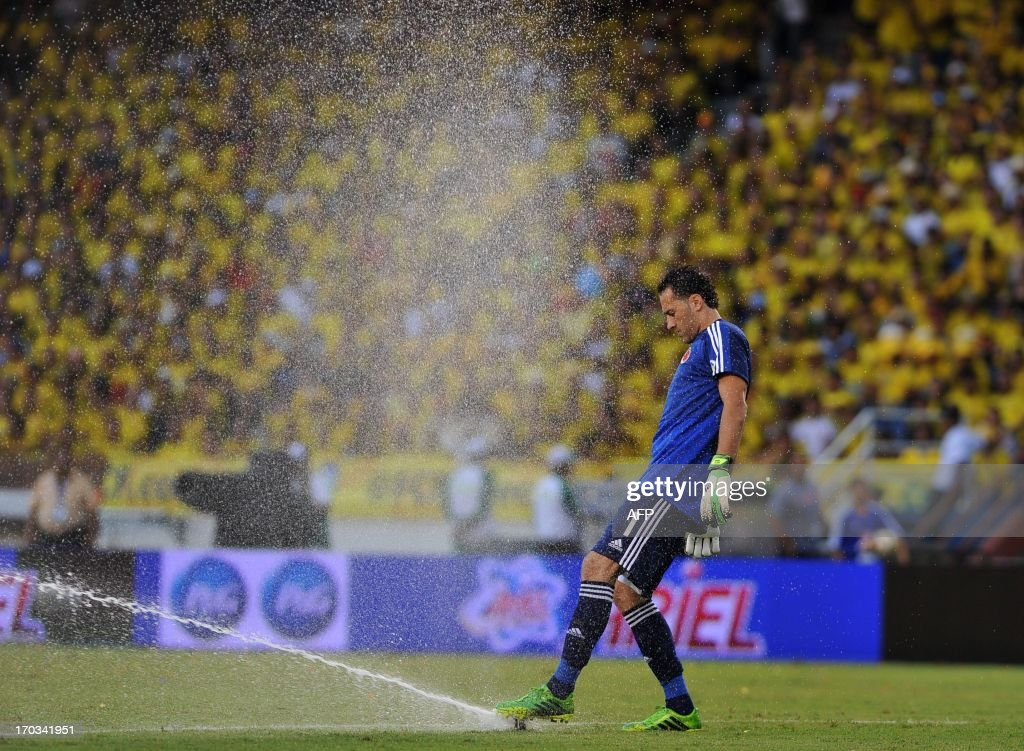 Colombian goalie David Ospina touchs with his foot an irrigator before the FIFA World Cup Brazil 2014 South American qualifier football match against Peru at the Metropolitan stadium in Barranquilla, Colombia, on June 11, 2013. AFP PHOTO/Luis ROBAYO