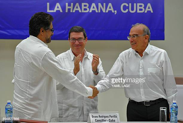 Colombian government head of delegation for peace talks Humberto de la Calle and FARCEP Commander Ivan Marquez shake hands upon the signing of the...