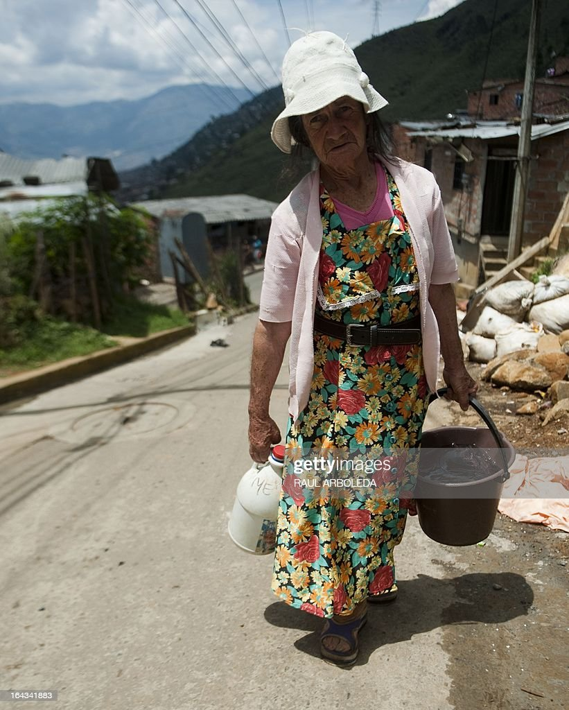 Colombian Graciela Restrepo, carry a bucket with water from a public tap in the 8th Commune in Medellin, Antioquia department, Colombia on March 22, 2013. The commune residents have to walk to collect water due to the lack of running water in the neighborhood. The World Water Day calls for international attention on the preservation of the world's drinking water resources. AFP PHOTO/ Raul ARBOLEDA