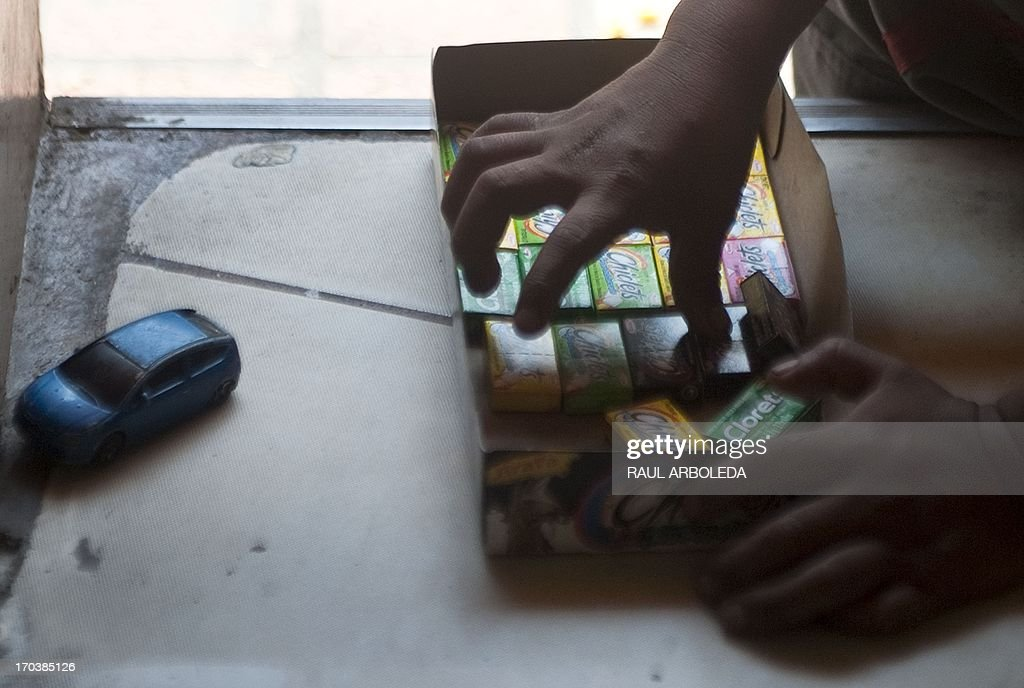 A Colombian indigenous boy who works selling candy along the streets of Medellin, Antioquia department, Colombia arranges his wares' box on June 12, 2013, during the World Day Against Child Labour. The day, first observed in 2002 and sanctioned by the International Labour Organization (ILO), aims to highlight the plight of children engaged in work that deprives them of adequate education, health, leisure and basic freedoms, violating their rights. AFP PHOTO/Raul ARBOLEDA