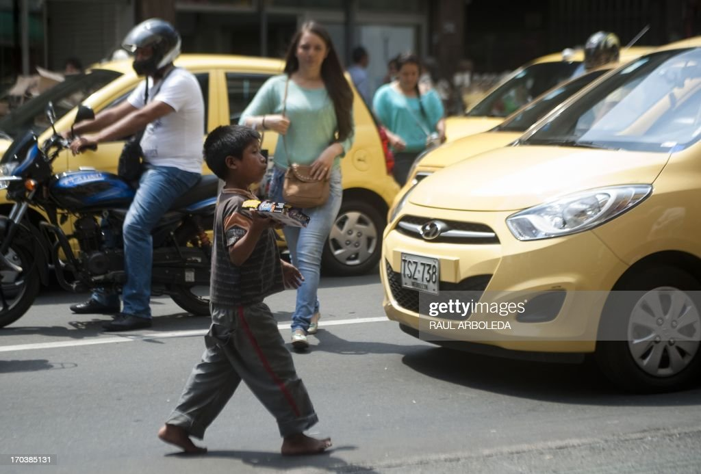 A Colombian indigenous boy works selling candy along the streets of Medellin, Antioquia department, Colombia on June 12, 2013, during the World Day Against Child Labour. The day, first observed in 2002 and sanctioned by the International Labour Organization (ILO), aims to highlight the plight of children engaged in work that deprives them of adequate education, health, leisure and basic freedoms, violating their rights. AFP PHOTO/Raul ARBOLEDA
