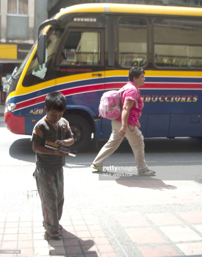 A Colombian indigenous boy (L) works selling candy along the streets of Medellin, Antioquia department, Colombia on June 12, 2013, during the World Day Against Child Labour. The day, first observed in 2002 and sanctioned by the International Labour Organization (ILO), aims to highlight the plight of children engaged in work that deprives them of adequate education, health, leisure and basic freedoms, violating their rights. AFP PHOTO/Raul ARBOLEDA