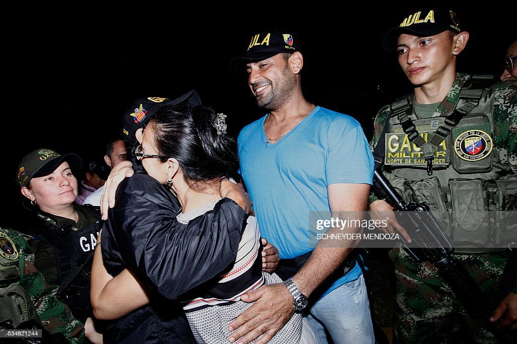 Colombian journalist Diego D'Pablos (2-R) and cameraman Carlos Melo (2-L), of Colombia's RCN television, greet their relatives on arrival at the airbase of Cucuta, Colombia, on May 28, 2016 following their release after being held by the ELN guerrillas for four days in the restive region of Catatumbo, Norte de Santander deparment, bordering Venezuela. The journalists were investigating the disappearance of Colombia-Spanish journalist Salud Hernandez, who disappeared on May 21, 2016. The Colombian rebel group ELN freed two local TV reporters and prominent Spanish-Colombian journalist Hernandez Mora on Friday after holding them for days. / AFP / Schneyder Mendoza
