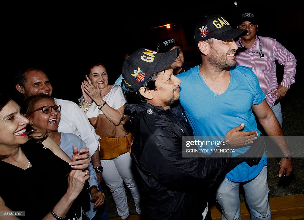 Colombian journalist Diego D'Pablos (R) and cameraman Carlos Melo (2-R), of Colombia's RCN television, greet their relatives on arrival at the airbase of Cucuta, Colombia, on May 28, 2016 following their release after being held by the ELN guerrillas for four days in the restive region of Catatumbo, Norte de Santander deparment, bordering Venezuela. The journalists were investigating the disappearance of Colombia-Spanish journalist Salud Hernandez, who disappeared on May 21, 2016. The Colombian rebel group ELN freed two local TV reporters and prominent Spanish-Colombian journalist Hernandez Mora on Friday after holding them for days. / AFP / Schneyder Mendoza