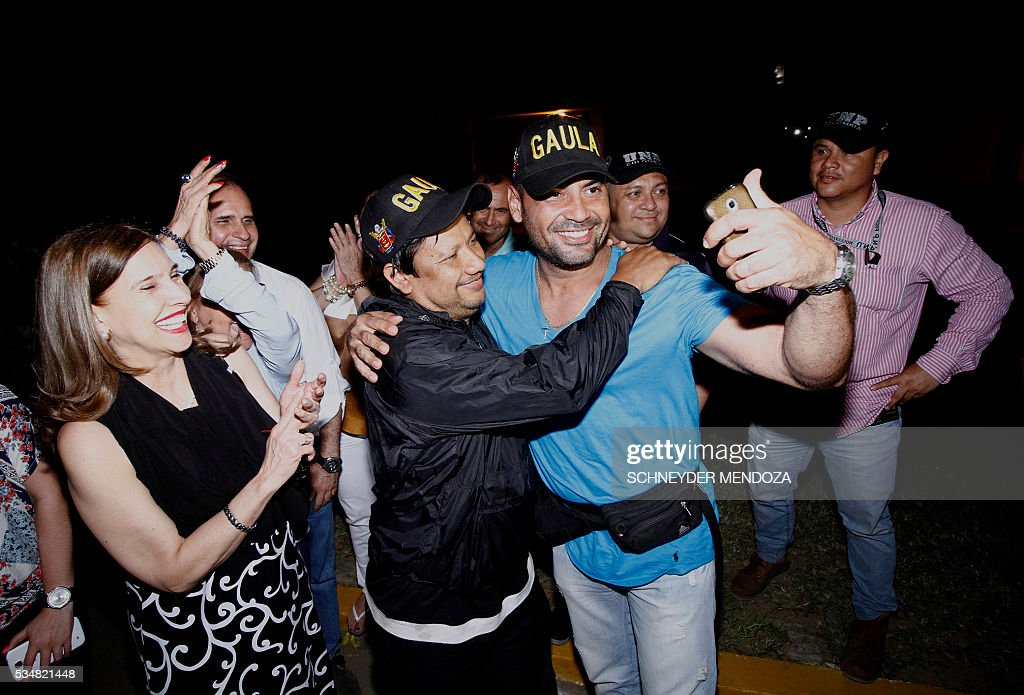 Colombian journalist Diego D'Pablos (R) and cameraman Carlos Melo, of Colombia's RCN television, take a selfie surrounded by relatives on arrival at the airbase of Cucuta, Colombia, on May 28, 2016 following their release after being held by the ELN guerrillas for four days in the restive region of Catatumbo, Norte de Santander deparment, bordering Venezuela. The journalists were investigating the disappearance of Colombia-Spanish journalist Salud Hernandez, who disappeared on May 21, 2016. The Colombian rebel group ELN freed two local TV reporters and prominent Spanish-Colombian journalist Hernandez Mora on Friday after holding them for days. / AFP / Schneyder Mendoza