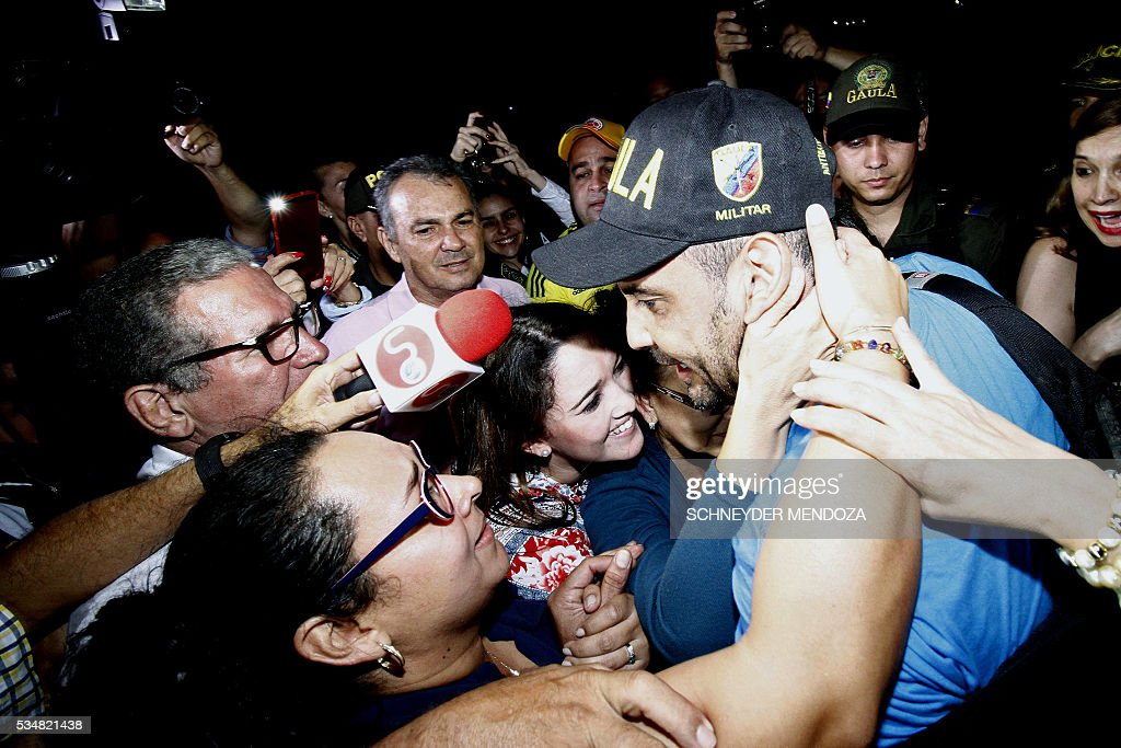Colombian journalist Diego D'Pablos (wearing cap), of Colombia's RCN television, greets relatives on arrival at the airbase of Cucuta, Colombia, on May 28, 2016 following his release after being held by the ELN guerrillas for four days in the restive region of Catatumbo, Norte de Santander deparment, bordering Venezuela. The journalists were investigating the disappearance of Colombia-Spanish journalist Salud Hernandez, who disappeared on May 21, 2016. The Colombian rebel group ELN freed two local TV reporters and prominent Spanish-Colombian journalist Hernandez Mora on Friday after holding them for days. / AFP / Schneyder Mendoza