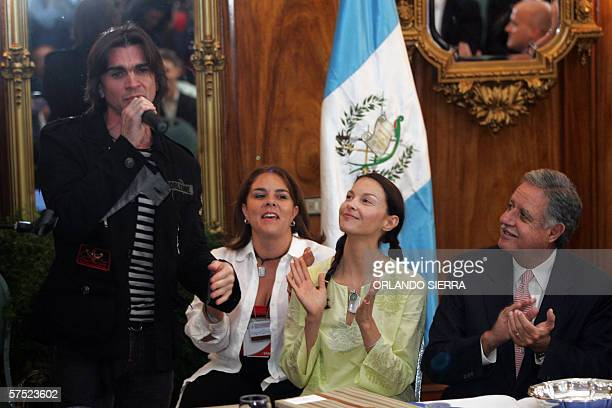 Colombian Juanes singns 'Camisa Negra' as Gutemalan President Oscar Berger and US actress Asheley Judd clap during a ceremony at the presidential...