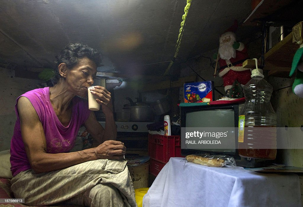 Colombian Maria Garcia drinks coffee inside a sewer on December 4, 2012, in Medellin, Antioquia department, Colombia. Garcia and her husband Miguel Restrepo, 62, are homeless and have lived for more than twenty years in a sewer, near Medellin's downtown. The place is around three by two by 1.4 meters of height and has a stove, a television, a bed and a fan. AFP PHOTO/Raul ARBOLEDA