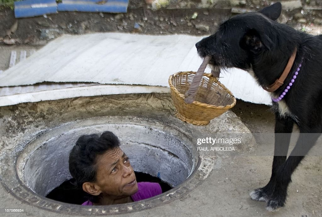 Colombian Maria Garcia looks at her dog frome the sewer where she lives on December 4, 2012, in Medellin, Antioquia department, Colombia. Garcia and her husband Miguel Restrepo, 62, are homeless and have lived for more than twenty years in a sewer, near Medellin's downtown. The place is around three by two by 1.4 meters of height and has a stove, a television, a bed and a fan. AFP PHOTO/Raul ARBOLEDA