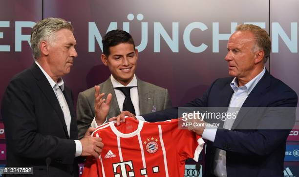 Colombian midfielder James Rodriguez new recruit of German first division Bundesliga football club Bayern Munich holds his new jersey as he poses...