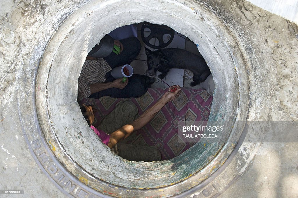 Colombian Miguel Restrepo (L, top) and his wife Maria Garcia feed their dog inside the sewer where they live on December 4, 2012, in Medellin, Antioquia department, Colombia. Restrepo, 62, is a homeless man who has lived with his wife for more than twenty years in a sewer, near Medellin's downtown. The place is around three by two by 1.4 meters of height and has a stove, a television, a bed and a fan. AFP PHOTO/Raul ARBOLEDA