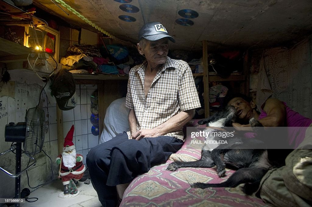 Colombian Miguel Restrepo (L), rests with his wife Maria Garcia and their dog on a bed inside a sewer on December 4, 2012, in Medellin, Antioquia department, Colombia. Restrepo, 62, is a homeless man who has lived with his wife for more than twenty years in a sewer, near Medellin's downtown. The place is around three by two by 1.4 meters of height and has a stove, a television, a bed and a fan. AFP PHOTO/Raul ARBOLEDA