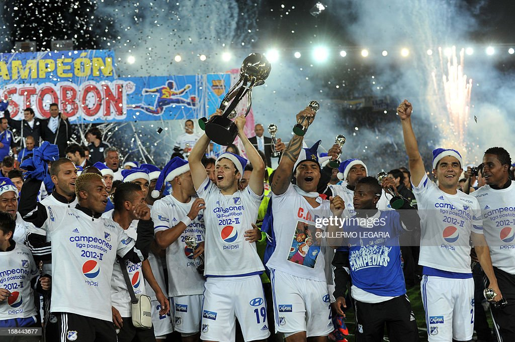 Colombian Millonarios players celebrate with the trophy after winning the Colombian League final football match against Deportivo Independiente Medellin at El Campin stadium in Bogota on December 16, 2012. AFP PHOTO/Guillermo Legaria