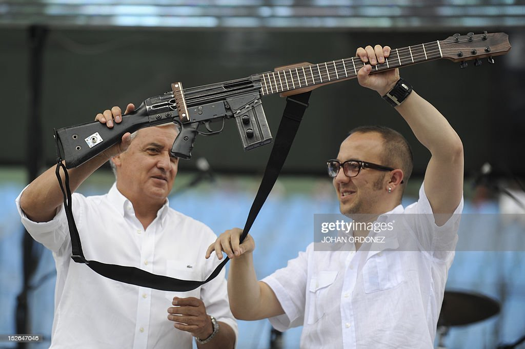 Colombian musician and Human Rights activist Cesar Lopez (R) hands an 'Escopetarra' -mixing of the words 'escopeta' (shotgun) and 'guitarra' (guitar)- to Guatemalan President Otto Perez Molina, during the 'Voices for Peace' concert at Mateo Flores stadium in Guatemala City on September 23, 2012. Thousands of Guatemalans attended a concert for peace and against violence. Guatemala registers an average of 16 daily deaths for different violent causes. AFP PHOTO / Johan ORDONEZ