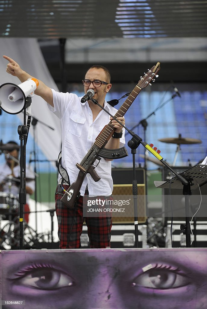 Colombian musician and Human Rights activist Cesar Lopez plays an 'Escopetarra' -mixing of the words 'escopeta' (shotgun) and 'guitarra' (guitar)-, during the 'Voices for Peace' concert at Mateo Flores stadium in Guatemala City on September 23, 2012. Thousands of Guatemalans attended a concert for peace and against violence. Guatemala registers an average of 16 daily deaths for different violent causes. AFP PHOTO / Johan ORDONEZ