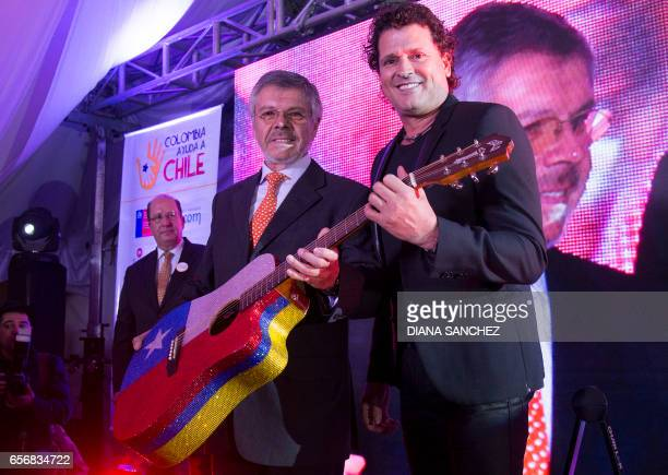 Colombian musician Carlos Vives and Ricardo Navarrete Ambassador to Chile in Colombia pose for pictures during Vives' guitar auction in Bogota on 22...