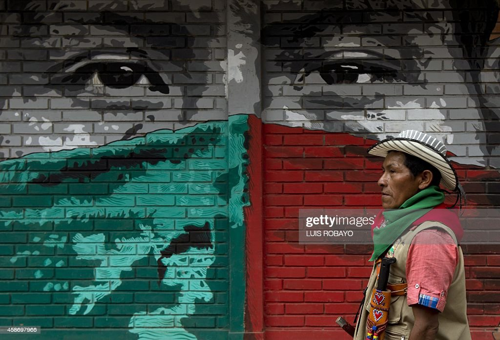 A Colombian Nasa native guard walks by a mural stencil before the start of the trial of seven alleged FARC members accused of murdering two leaders of their tribe, on November 9, 2014, in Toribio, department of Cauca, Colombia. When crimes are committed in aboriginal territory, the punishment for the accused is decided by the community and not the ordinary justice system. The suspected Revolutionary Armed Forces of Colombia (FARC) rebel fighters on Wednesday attacked two native leaders who were removing billboards praising the late leader of the Revolutionary Armed Forces of Colombia, Guillermo Leon Saenz, also known as Alfonso Cano. AFP PHOTO / LUIS ROBAYO