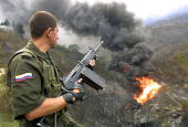 Colombian National Police officer watches a fire 05 March caused by an explosion at a oil pipeline in the Medellin neighborhood of Paris According to...