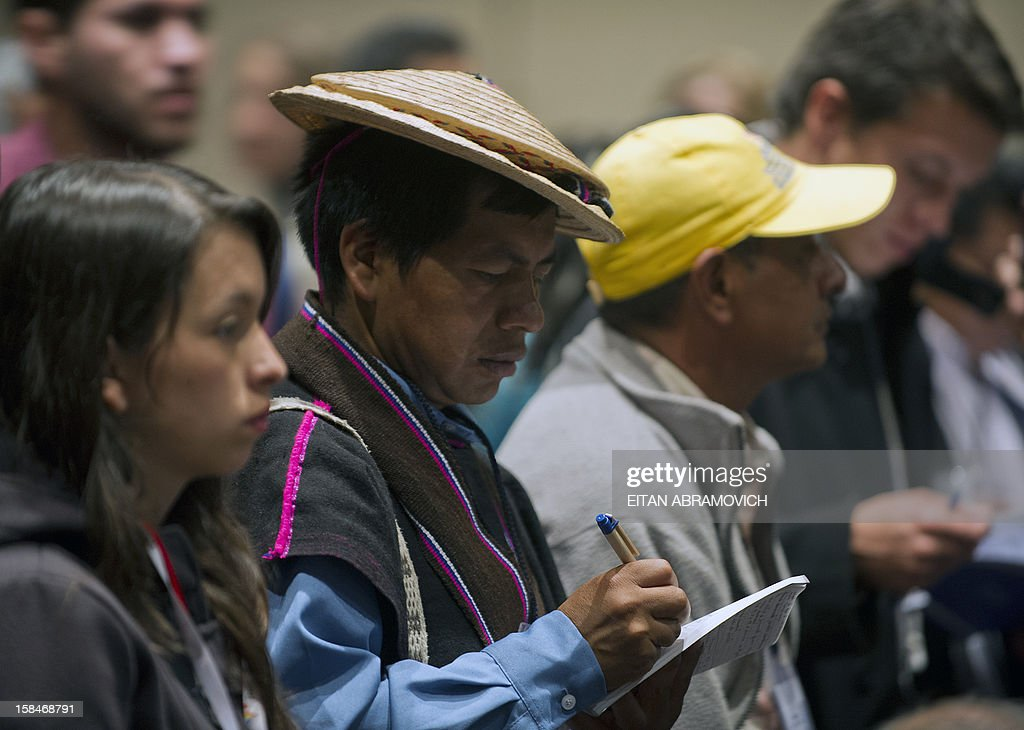 A Colombian native takes notes during a forum on agricultural policy in Bogota, Colombia, on December 17, 2012, in the sidelines of the peace talks that Colombia's government and the FARC rebel group are holding in Cuba. AFP PHOTO/Eitan Abramovich