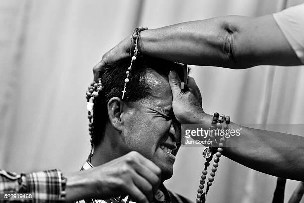Colombian pastor pressing a crucifix on a believer's head attempts to evict a supposed demon during the exorcism ritual performed at a house church...
