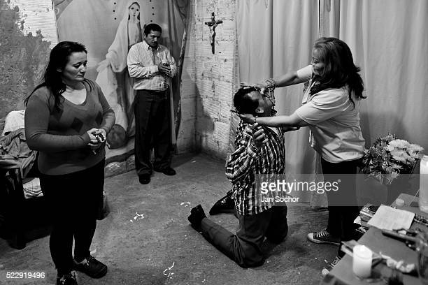 Colombian pastor pressing on a believer's head attempts to evict a supposed demon during the exorcism ritual performed at a house church on March 10...