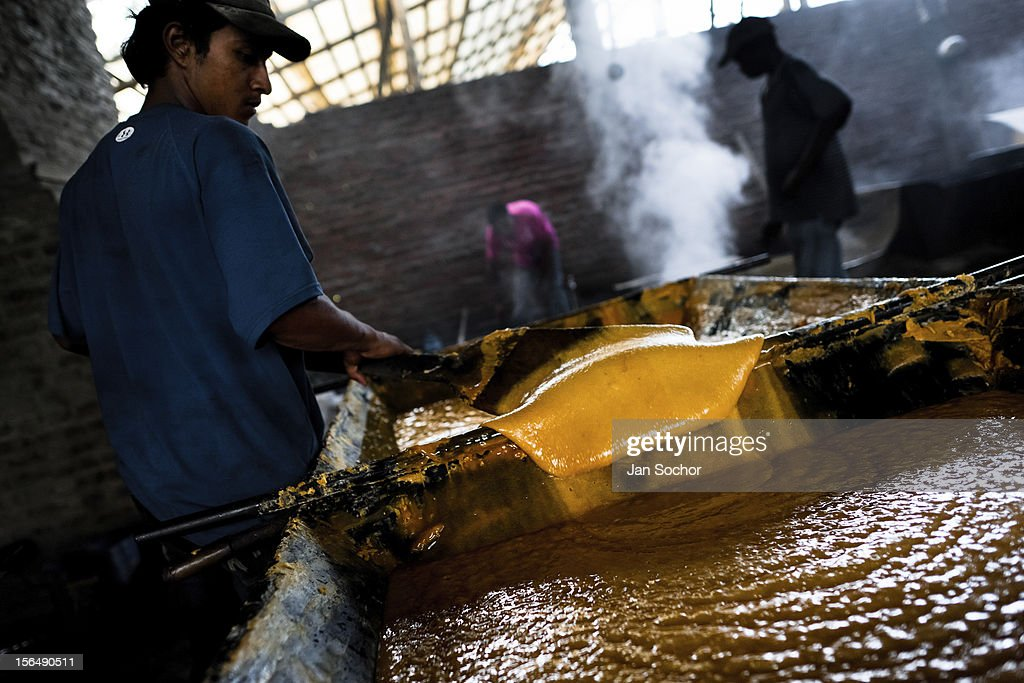 A Colombian peasant mixes a hot mass of sugar cane juice during the processing of panela in a rural sugar cane mill (trapiche) on 30 May 2012 in in Santa Ana, Valle del Cauca, Colombia. Panela, a solid block of raw, unrefined sugar, is made by cooking and evaporation of the sugar cane juice into a golden, sticky syrup which is then poured into the wooden molds and allowed to solidify. Having the taste like a cross between molasses and brown sugar, panela is served as a hot or cold infusion called aguapanela. Due to the large amounts of proteins, vitamins and minerals and thus, panela is believed to have healing powers. Cheaper than sugar, it is consumed by the majority of Colombians and it is a major source of calories for children from families with low socioeconomic status. With more than 70,000 farms that cultivate sugarcane for mills, panela production is an important economic activity in the Colombian countryside, employing around 350,000 people and being the second largest source of jobs after agricultural coffee production.