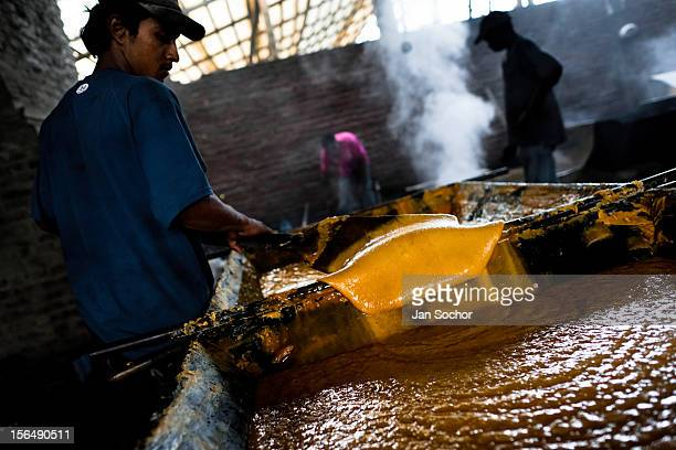Colombian peasant mixes a hot mass of sugar cane juice during the processing of panela in a rural sugar cane mill on 30 May 2012 in in Santa Ana...