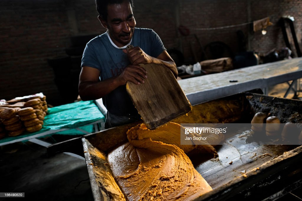 A Colombian peasant mixes a hot mass of sugar cane juice during the processing of panela in a rural sugar cane mill (trapiche) in Santa Ana, Valle del Cauca, Colombia, 30 May 2012. Panela, a solid block of raw, unrefined sugar, is made by cooking and evaporation of the sugar cane juice into a golden, sticky syrup which is then poured into the wooden molds and allowed to solidify. Having the taste like a cross between molasses and brown sugar, panela is served as a hot or cold infusion called aguapanela. Due to the large amounts of proteins, vitamins and minerals and thus, panela is believed to have healing powers. Cheaper than sugar, it is consumed by the majority of Colombians and it is a major source of calories for children from families with low socioeconomic status. With more than 70,000 farms that cultivate sugarcane for mills, panela production is an important economic activity in the Colombian countryside, employing around 350,000 people and being the second largest source of jobs after agricultural coffee production.