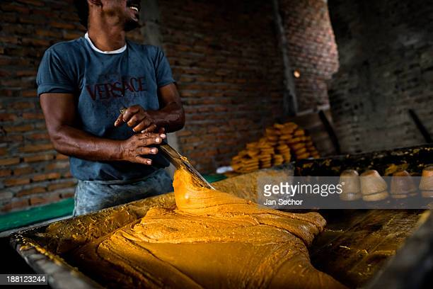 Colombian peasant mixes a hot mass of sugar cane juice during the processing of panela in a rural sugar cane mill in Santa Ana Valle del Cauca...