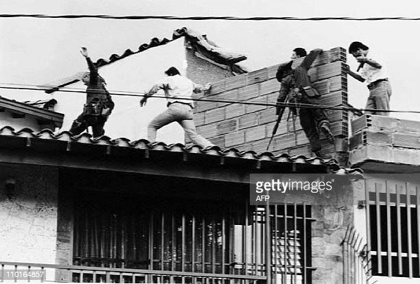 Colombian police and military forces storm the rooftop where drug lord Pablo Escobar was shot dead just moments earlier during an exchange of gunfire...