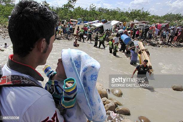 Colombian police help Colombian citizens carry their belongings as they cross the Tachira border river from Brisas de Barinitas Tachira state...