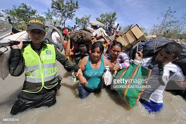 Colombian police help Colombian women carry their belongings as they cross the Tachira border river from Brisas de Barinitas Tachira state Venezuela...