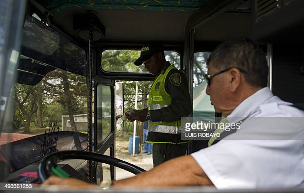 A Colombian police officer checks the IDs of the passengers traveling on a bus in Cali Colombia on May 23 2014 Colombia's presidential elections will...